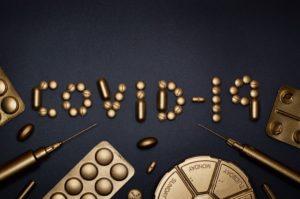 scritta covid-19 realizzata con pillole e siringhe