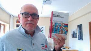 Presidente IICBIM Ing. Stefano Antonelli mentre scatta un selfie con in mano un libro di Project Management di Russel D. Archibald