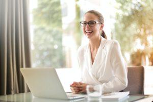 giovane donna professionista che sorride alla postazione di lavoro presumibilmente nell'ambito del project management