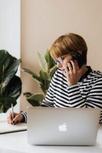 ragazza in smartworking con computer apple sulla scrivania e il cellulare in mano mentre sta al telefono