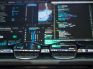 computer con schermo programmi di programmazione e occhiali in primo piano appoggiati sulla tastiera del computer