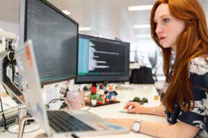 giovane programmatrice al lavoro su un desk con due schermi al computer